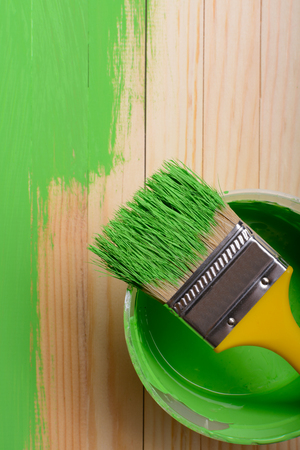 Green paint with a brush on wooden slats: top view