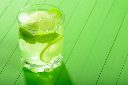 A glass of Mojito with ice, limes and mint on wooden boards Stock Photo