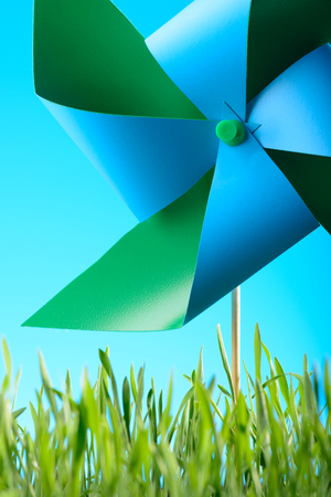 Windmill toy on green grass against the sky Stock Photo