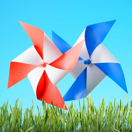 Windmills toys on green grass against the sky
