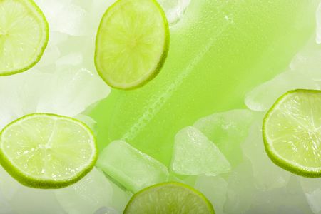 A bottle of lemonade with lime on ice Stock Photo