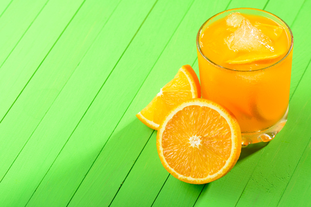 A glass of orange juice with ice on green wooden table