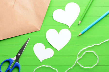 Stickers in the shape of a heart with an envelope on green wooden background Stock Photo