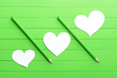 stylus: Stickers in shape of heart on green wood background
