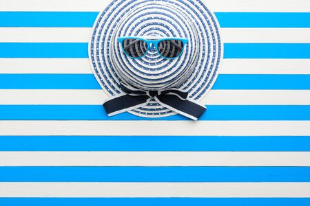 Striped hat and sunglasses on blue-white background. Top view, flat lay. Stock Photo