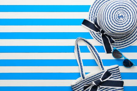 Beach accessories on a blue and white background. Top view, flat lay.