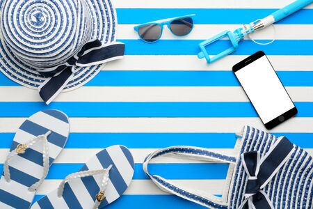 Beach accessories and smartphone on white and blue background. Top view, flat lay.