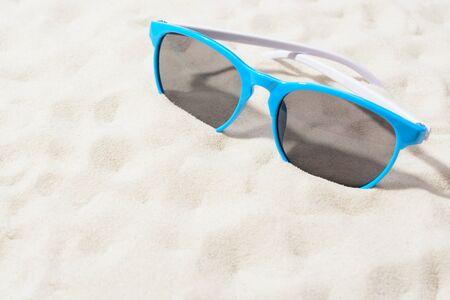 砂の上の明るいサングラス