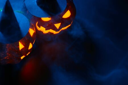 Two Halloween pumpkins with carved faces decorated with black witch hats glowing in smoke