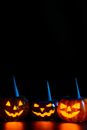 Three spooky carved pumpkins in black witch hats on table in darkness