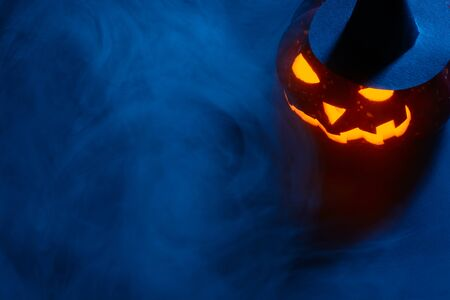 Composed glowing carved pumpkin in black witch hat lying on surface in mist