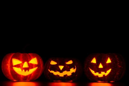 Three spooky carved pumpkins on table in darkness Stock Photo