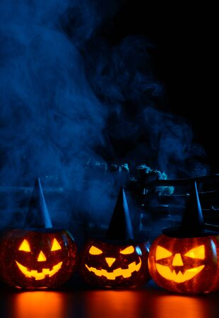 Three glowing carved pumpkins in witch hats behind wooden fence in mist
