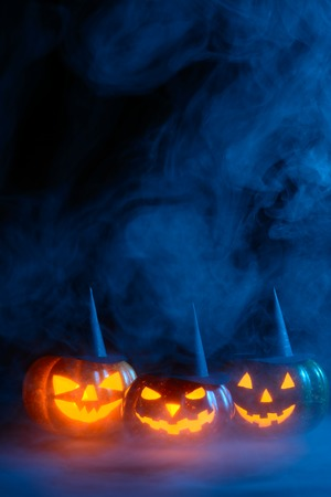 Three Halloween pumpkins with carved faces decorated with black witch hats glowing in smoke