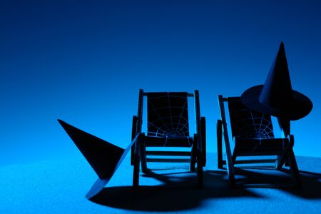 Creative composition of beach chairs with black witch hats in moonlight Stock Photo
