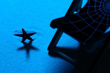 Van boven schot van strandstoel en parasol op zand met zee ster Stockfoto