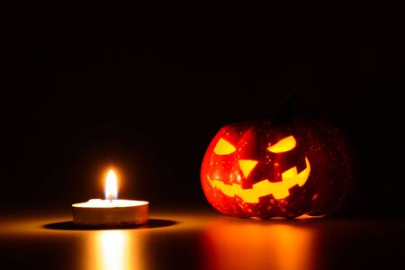 Pumpkin-made lantern for Halloween and row of lighting candles