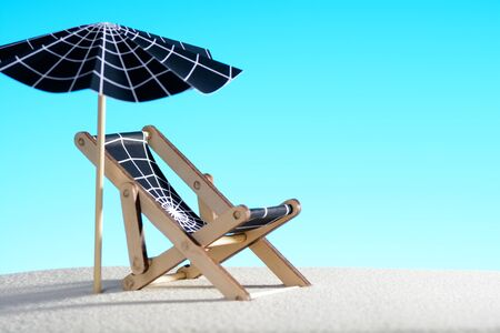 Lounge chair and umbrella with spider web on sand