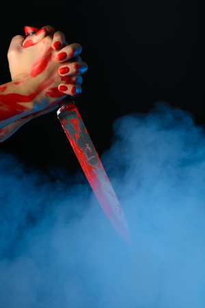 Blood womans hand holding the bloody knife against the smoky background Reklamní fotografie