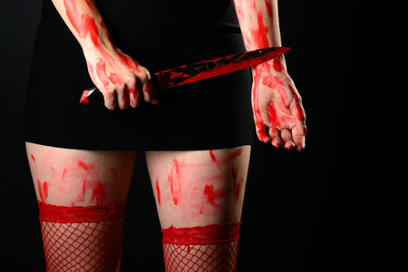 Mid section of woman wearing red stockings holding bloody knife 版權商用圖片