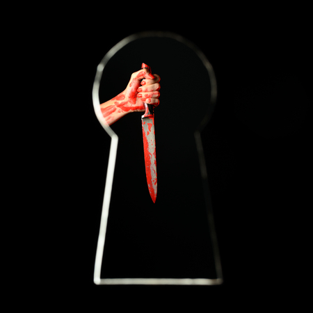 Bloodstained female hand holding bloody knife seen through keyhole 版權商用圖片