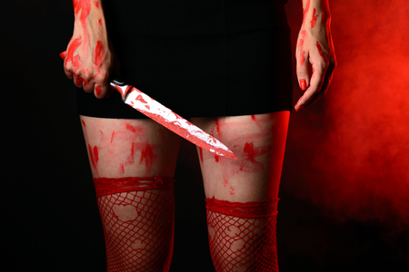 Mid section of woman wearing red stockings holding bloody knife in hand against smoky background