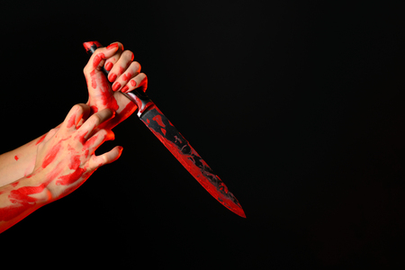 Blood womans hand holding the bloody knife