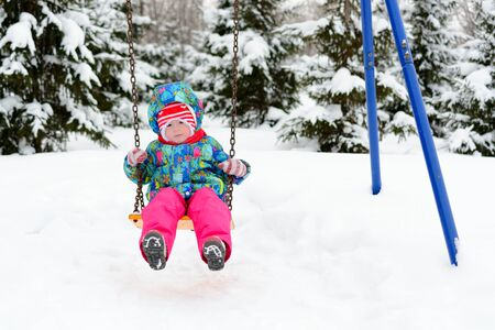 playground rides: Little girl rides a swing on the Playground in winter