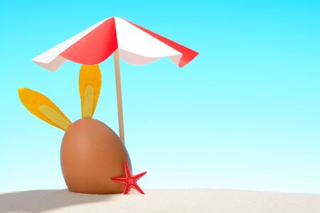 Cute bunny decorated Easter egg under umbrella on sunny sandy beach Stock Photo