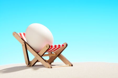 Easter egg in lounger�on sandy beach