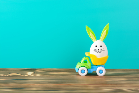 Creative arrangement of chicken egg with decorative bunny ears and snout riding in toy truck