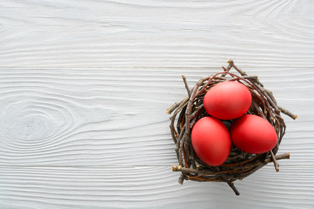Easter background with red eggs in the nest on wooden table. Top view with copy space