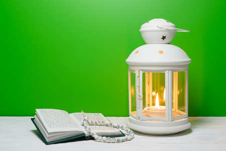 Bright lantern and Holy Book Quran. Ramadan Kareem background with copy space