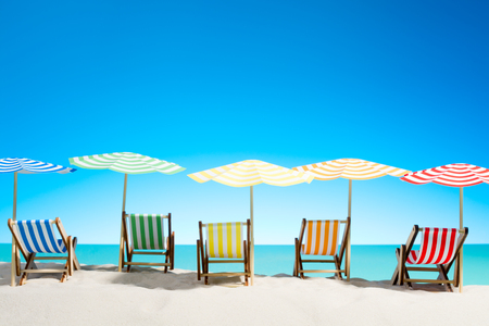 Multi-colored sun loungers with umbrellas on the sandy beach, sky with copy space