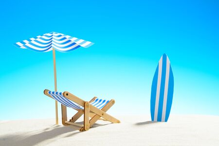 Deck chair under an umbrella and a surfboard on sandy beach, sky with copy space Stock Photo