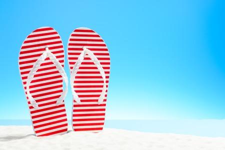 Red striped flip flops on a sandy beach Foto de archivo