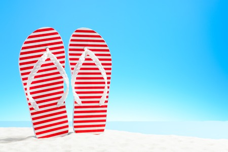 Red striped flip flops on a sandy beach Фото со стока