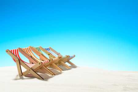 Multi-colored lounge chairs in a row on the sandy beach. Sky with copy space