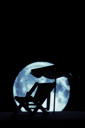The silhouette of a lounger on the background of the full moon