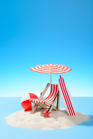 Paradise island in the ocean. Miniature beach accessories for outdoor activities. Blue background with copy space Stock Photo