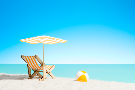 Lounge chair with parasol and beach ball on the coast, sky with copy space Stock Photo
