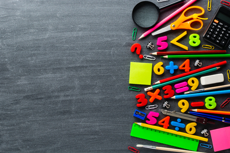 Assorted school supplies and simple math exercises lying on surface of clean blackboard.  Imagens