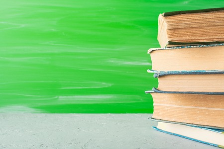Bunch of old textbooks standing on bright green background.