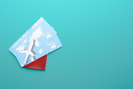 Two plane tickets lying in passport with red cover on left side of turquoise background