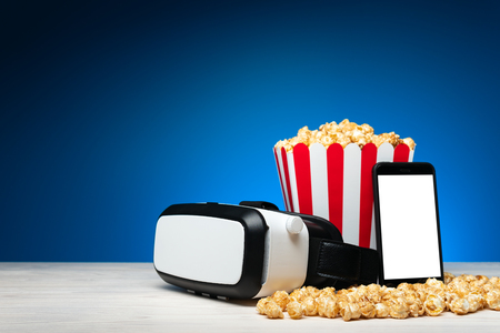 Arrangement of modern headset of virtual reality with smartphone and colorful bucket of popcorn on blue background