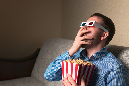 Handsome adult guy in 3D glasses covering mouth in shock while eating popcorn and watching movie on comfortable sofa Imagens