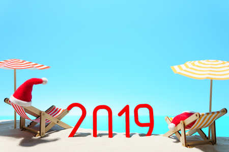 Colorful 2019 New Year celebration on beach with deck chairs under sunshades in sunlight