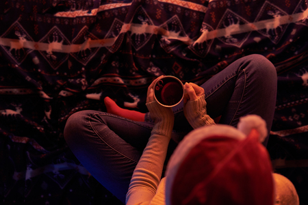 From above shot of woman in Santa hat sitting with mug on plaid in soft light