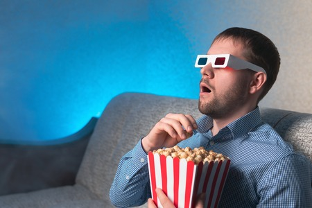 Handsome adult male in 3D glasses eating popcorn and watching movie with astonished face expression while sitting on couch in cozy room