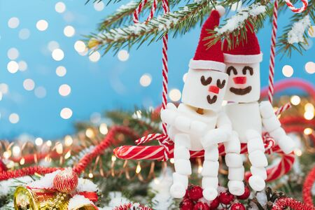 Two lovers of Marshmallow snowmen are sitting on a swing of candy. Christmas meeting a couple in love concept.